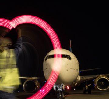 Foto noturna de avião, com luzes formando um coração