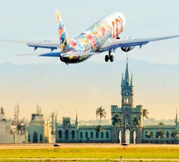 Foto de avião decolando em aeroporto do Rio de Janeiro com monumento histórico de fundo