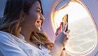 Mulher dentro de avião fotografando a paisagem na janela