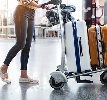 Mulher empurrando um carrinho cheio de malas de viagem no aeroporto