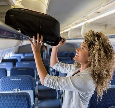 Passageira colocando bagagem de mão no compartimento superior da aeronave
