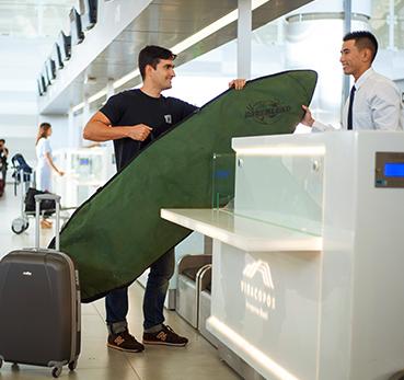 Passageiro fazendo check-in no aeroporo e despachando uma prancha de surf