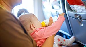 Pai dando mamadeira para bebê no avião