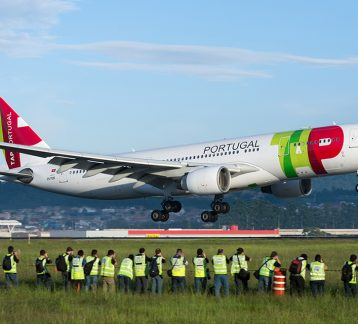 Foto de avião da TAP decolando no aeroporto de Guarulhos e sendo fotografado por dezenas de spotters