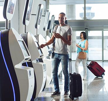 Homem fazendo check-in em totem de autoatendimento em aeroporto