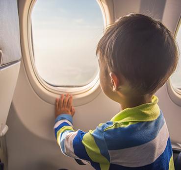 Criança sentada dentro de avião observando a janela