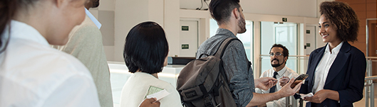 Funcionária recebe passageiros no check-in