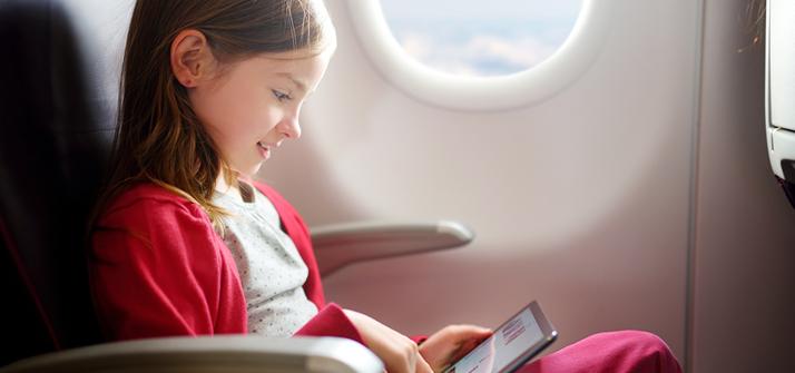 Criança sozinha na poltrona de um avião brincando com iPad.
