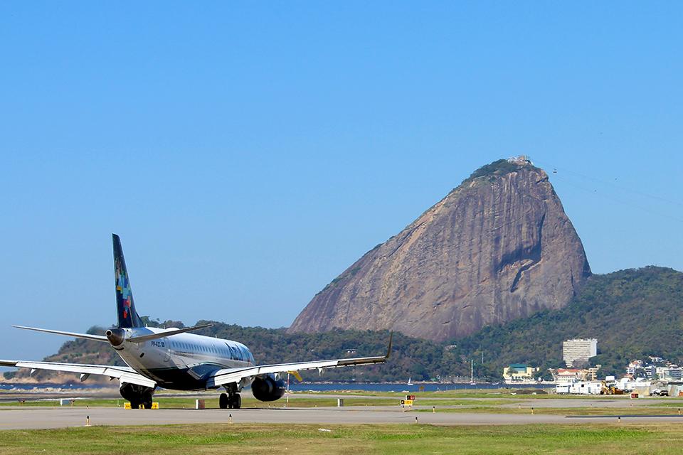 Avião na pista de decolagem e, ao fundo, o Pão de Açúcar, no Rio de Janeiro