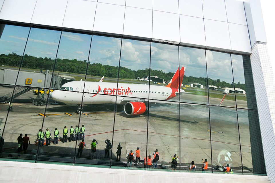 Avião da Avianca fotografado em reflexo dos vidros espelhados de um prédio do aeroporto