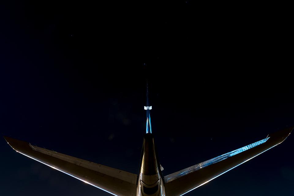 Foto noturna de cauda de avião vista de baixo para cima