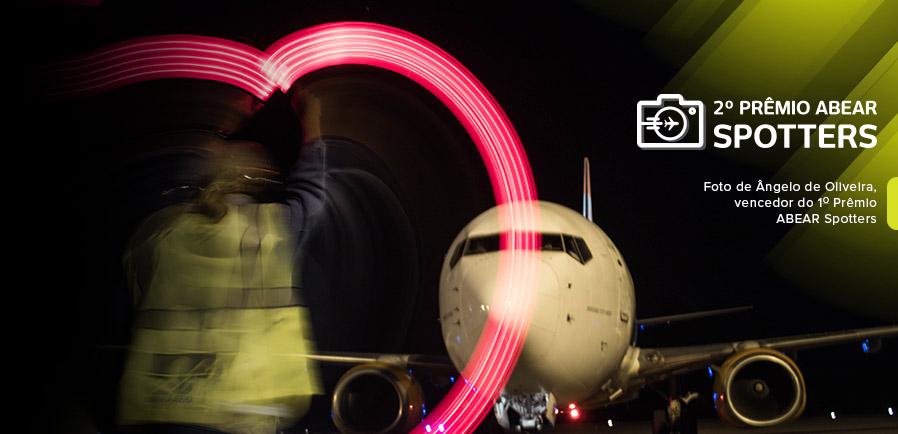 Funcionário de pista usando sinalizadores luminosos formando um coração de luz na frente de um avião que está estacionado na pista